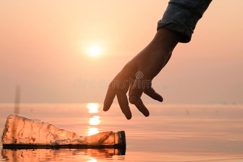 Hand Woman picking up empty of plastic bottle cleaning on the beach , volunteer concept. Environmental pollution. Ecological problem stock photo