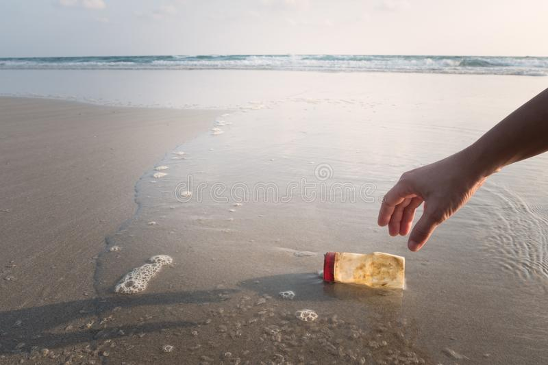 The hand of a woman is picking up a plastic bottle to clean the. Beach royalty free stock photo