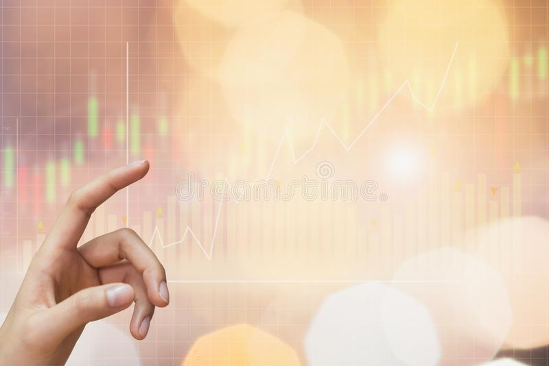 The hand of the woman is pointing and show graph with the stock exchange trading graph. The hand of the woman is pointing and show graph with the stock exchange royalty free stock photos