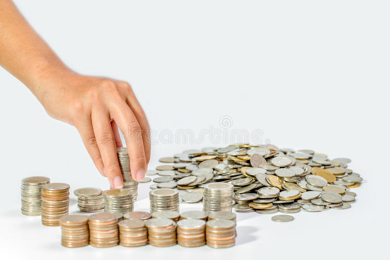 Hand of woman putting coin to rising stack of coins, Saving money concept. stock photography