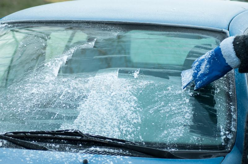 hand of woman scraping frost on the windscreen of car royalty free stock images
