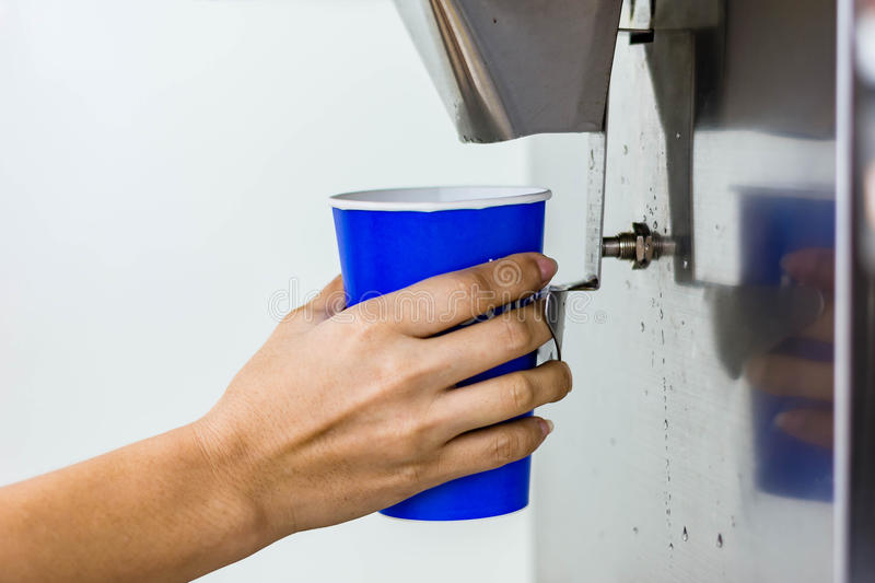 Hand of woman serving ice of ice maker machine stock photography