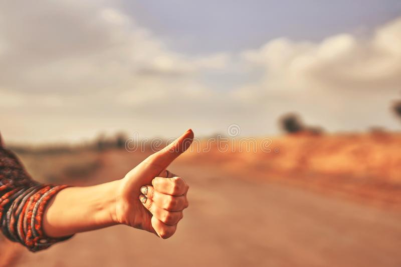 Hand of woman traveler. Hand of woman tourist hitchhike with thumbs up form the asphalt road go to travel at autumn stock images