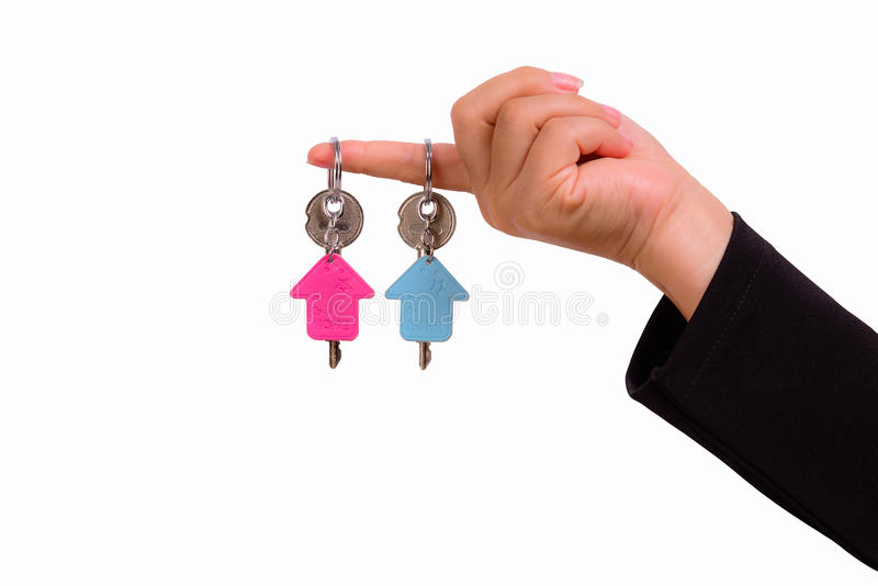 Hand of woman with two keychain in the shape of the house. Isolated on white background royalty free stock photo