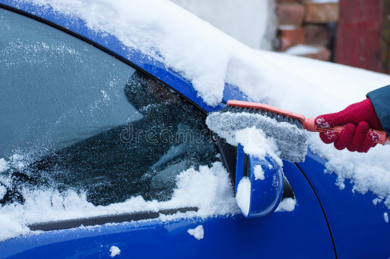 Hand of woman using brush and remove snow from car, windscreen and mirror. Hand of woman using brush and remove snow and ice from car, windscreen and mirror royalty free stock photography