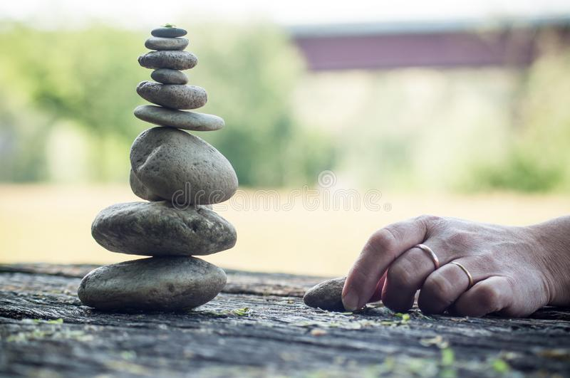 Hand of woman waiting for another stone for balance royalty free stock images