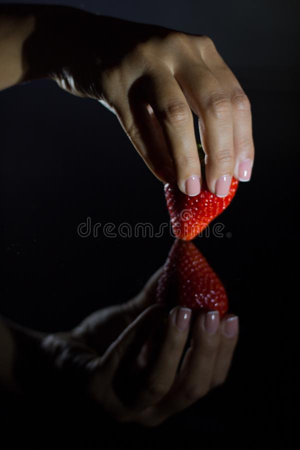 The hand of a woman who takes a strawberry and its reflection with black background royalty free stock photography