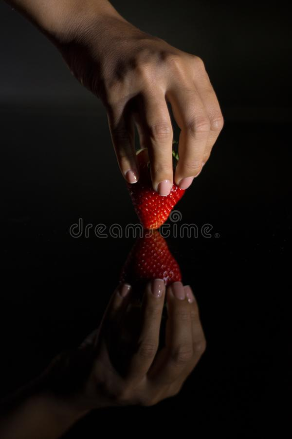 The hand of a woman who takes a strawberry and its reflection with black background stock image