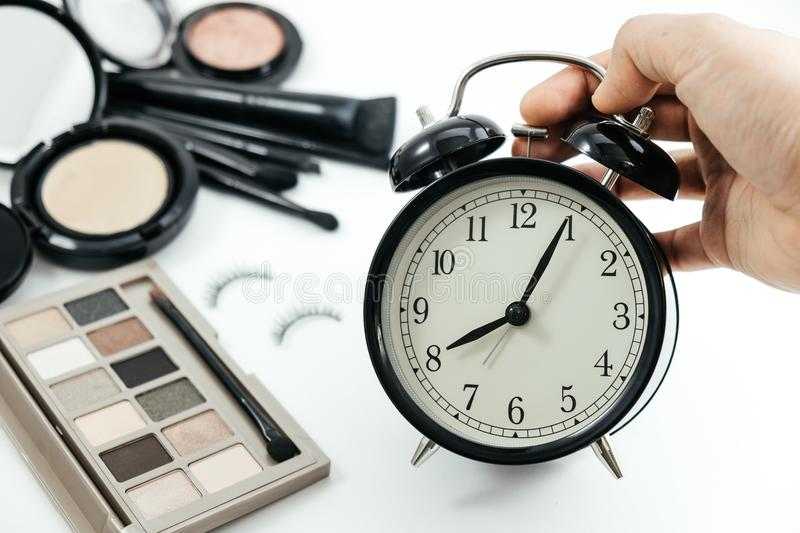 Hand of women hold clock and cosmetic object, powder on white ta stock photo