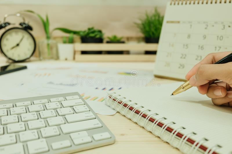 hand of women hold pen prepared for write on notebook has keyboard placed beside. with info graph, clock, calendar and plants are royalty free stock photos