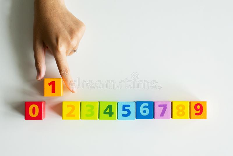 Hand women pointing wood block one,Concept of number 1 and top winner success,Top view copy space for text stock images