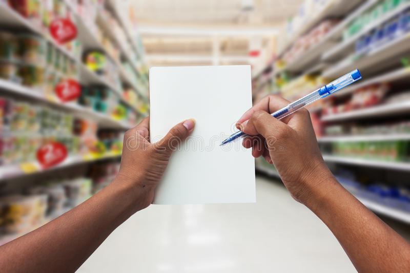Hand women shopping and holding empty notebook. For check list her buy in the supermarket stock photos