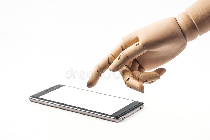 Hand of wood doll make fingers to touch with smart phone on white background royalty free stock images