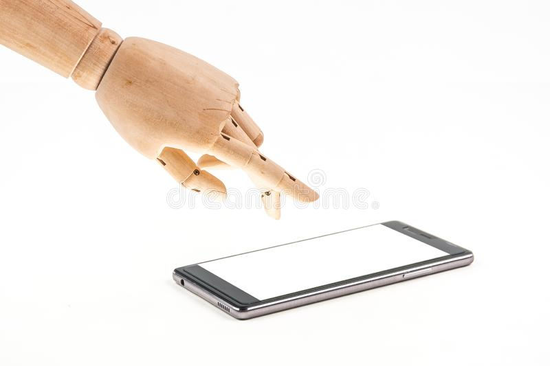 Hand of wood doll make fingers to touch with smart phone on white background royalty free stock photo