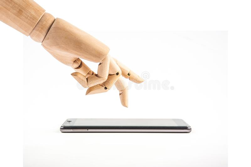 Hand of wood doll make fingers to touch with smart phone on white background royalty free stock photography