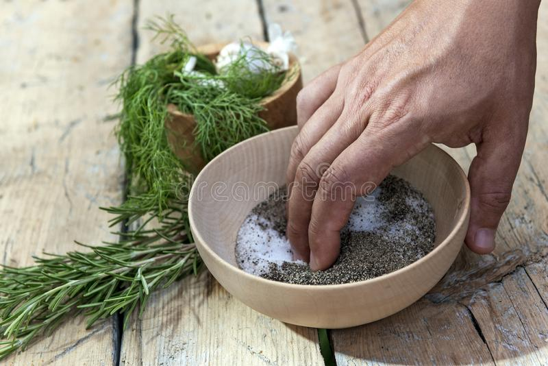 Hand in a wooden bowl mixes salt and pepper royalty free stock images