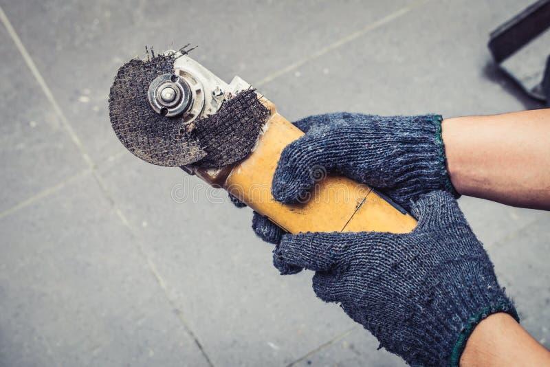 Hand of worker man hold Grinder blades broken . Dangers of using stock photography