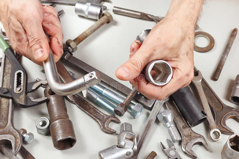Hand of worker with repairing parts of mechanism in workshop royalty free stock image