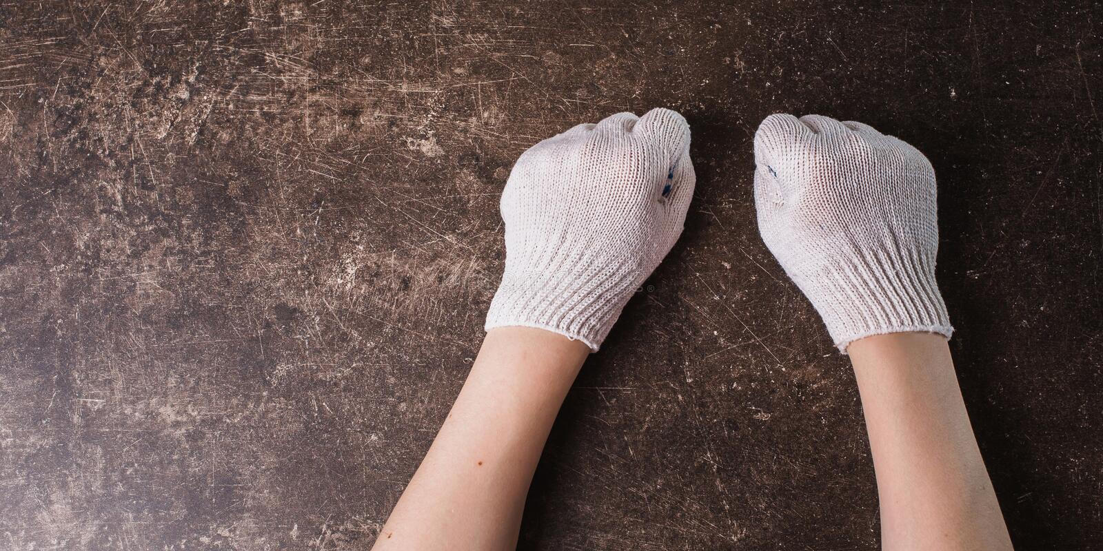 Working gloves on a dark marble background. Hand in working gloves on a dark marble background. Tidy up the house. Do makeovers stock photography
