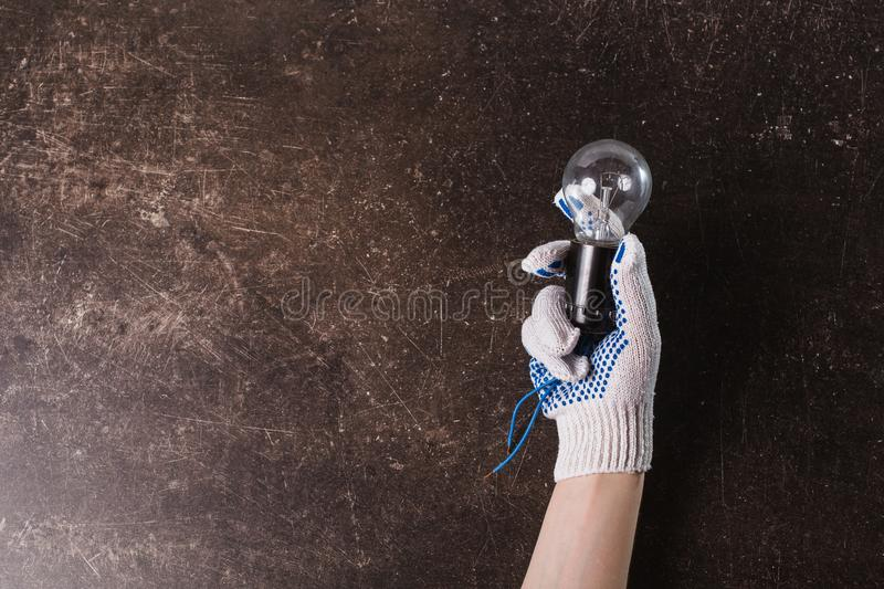 Working gloves on a dark marble background. Hand in working gloves with a light bulb on a dark marble background royalty free stock photography