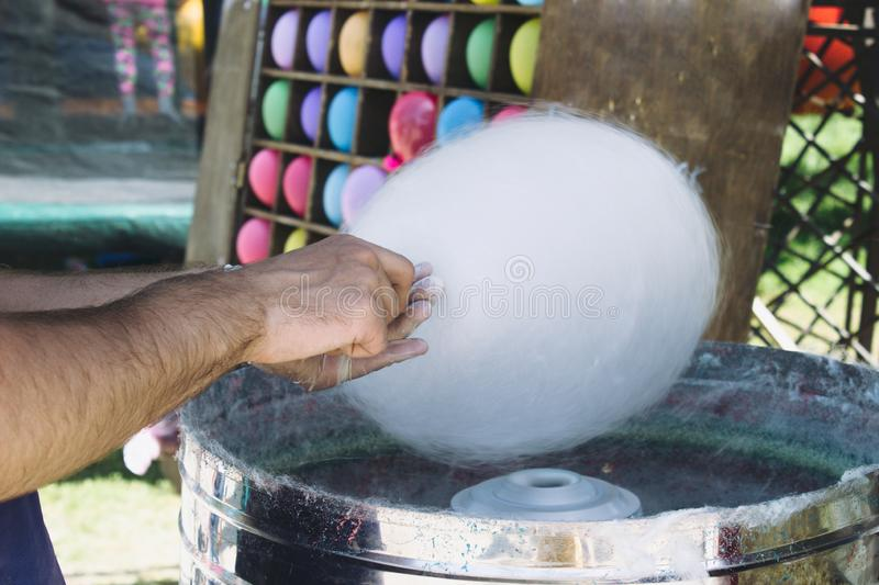 A hand wrap a cotton candy on a stick in a cotton candy machine. Making cotton candy royalty free stock photos