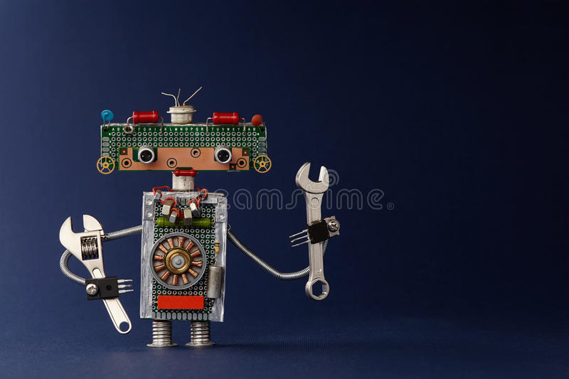 Hand wrench adjustable spanner robot handyman on dark blue paper background. Cute robotic toy made of electronic. Circuits, chip capacitors vintage resistors royalty free stock images