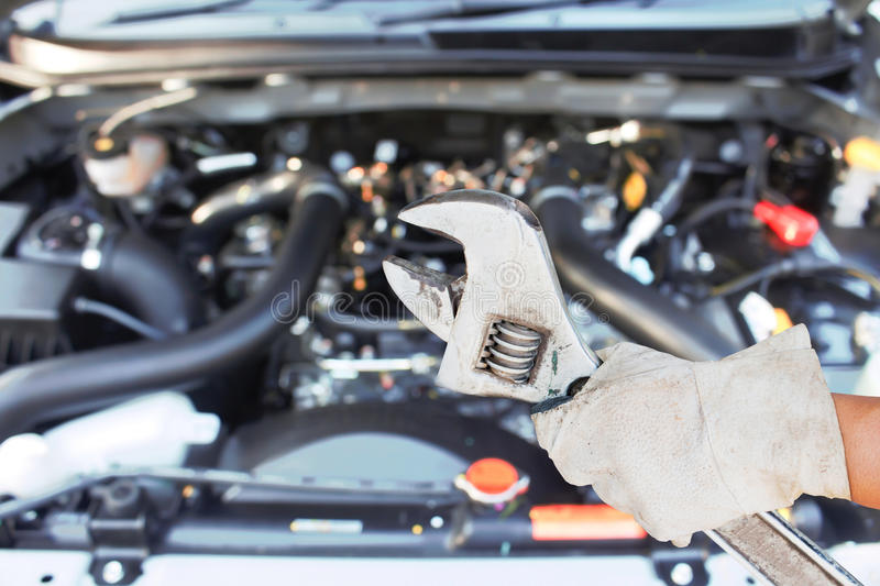 Hand with wrench checking car engine. royalty free stock images