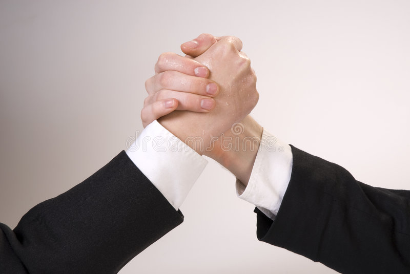 Hand wrestling. Portrait of two businessmen sitting opposite each other elbowing on the table with their arms grappled in fight stock photos