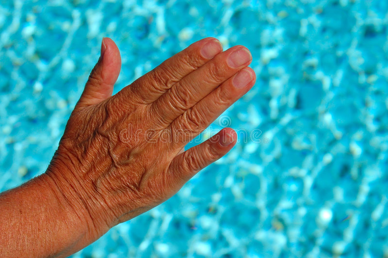Hand with wrinkles. An old wrinkled female caucasian hand touching the fresh sparkling water of a swimming-pool royalty free stock photo