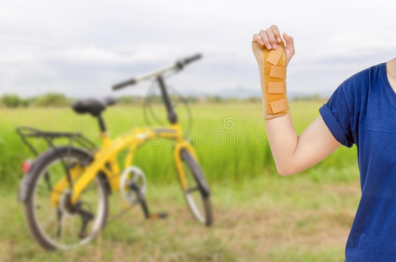 Hand with a wrist brace, orthopedic equipment with yellow bicycle in green filed. royalty free stock photo