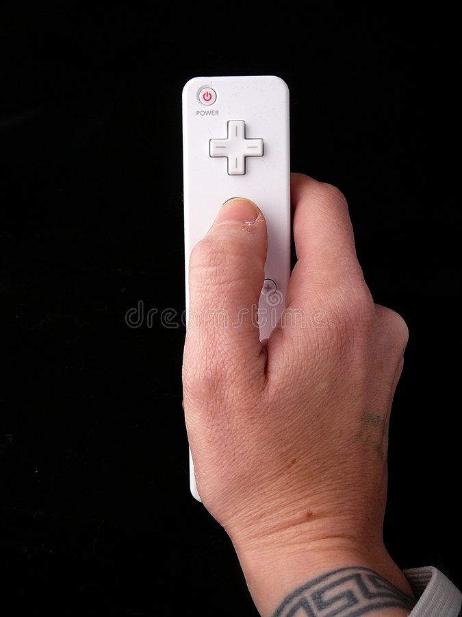 Hand with wrist tattoo holding. Video game control over black background royalty free stock image