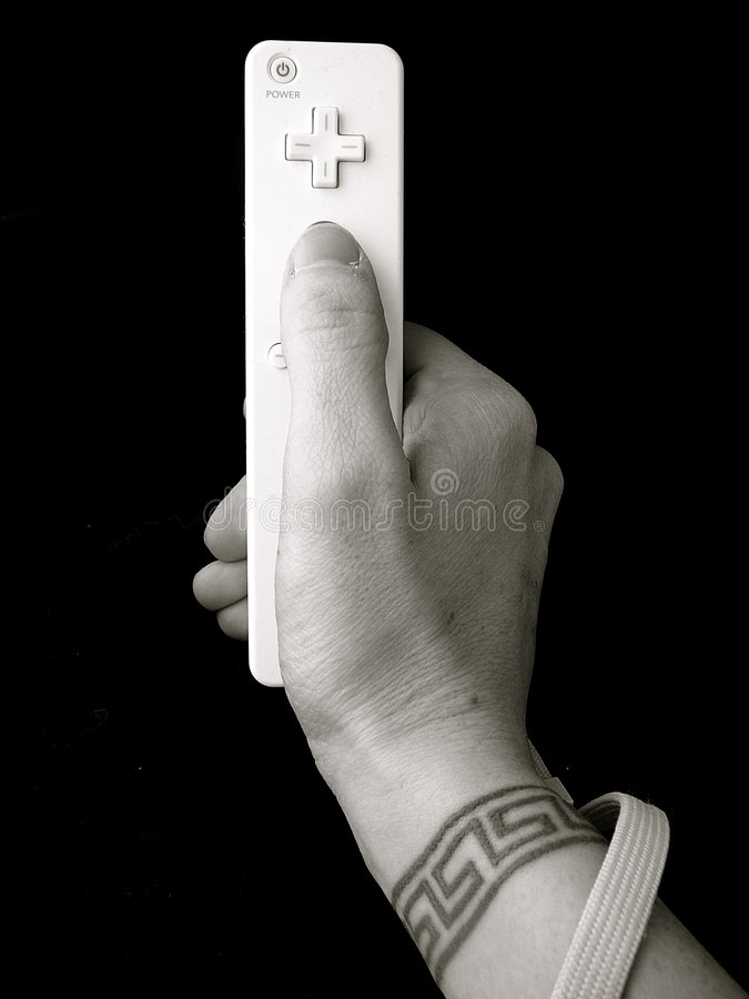 Hand with wrist tattoo holding video game control royalty free stock photo