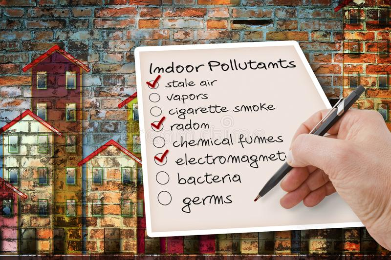 Hand write a check list of indoor air pollutants against a buildings background.  royalty free stock photos