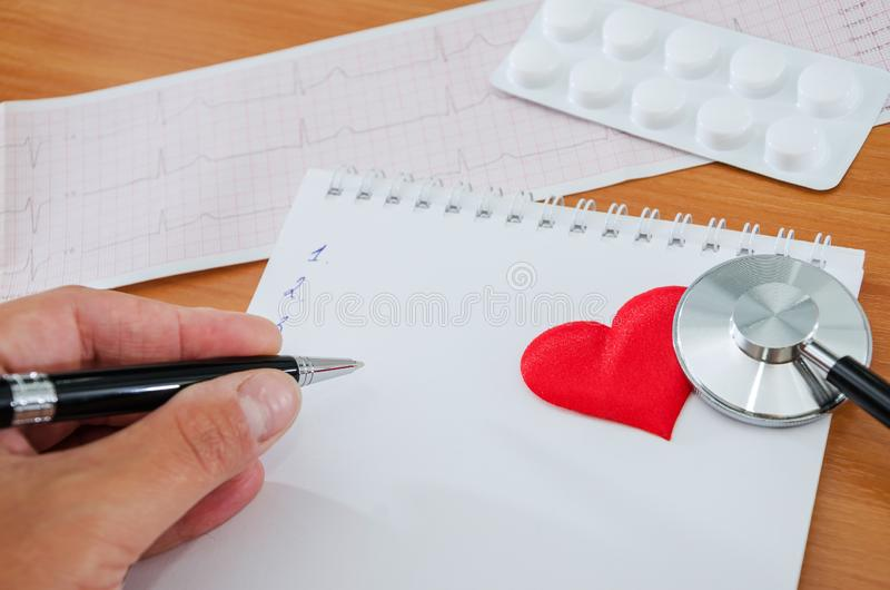 Hand writes on a notepad. Stethoscope, heart, pills, cardiogram on a wooden background stock photography