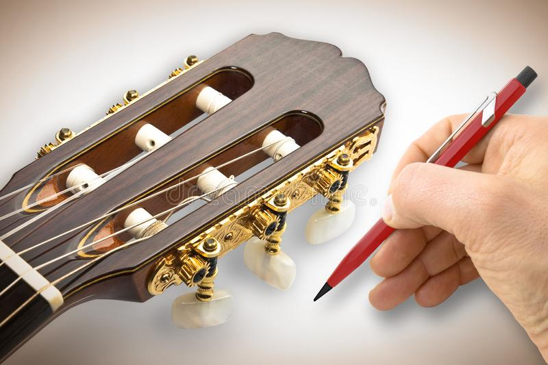 Hand writing above a background with acoustic classical guitar stock photo