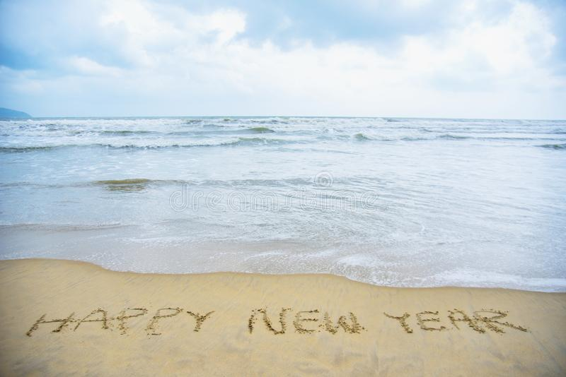 Happy new year on the beach. Hand writing on the beach for happy new year background stock image