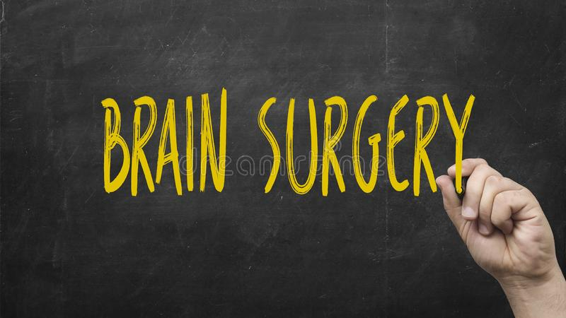 Hand writing Brain Surgery on black chalkboard. Hand writing Brain Surgery yellow marker on black chalkboard royalty free stock image