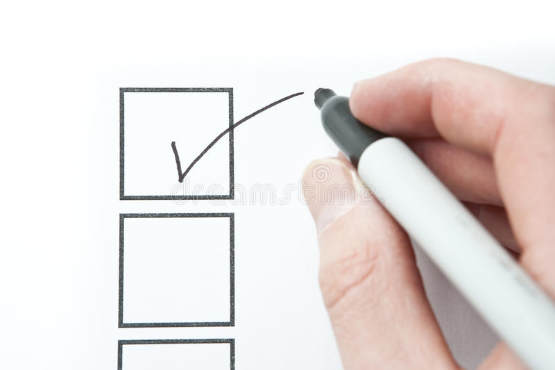 Hand Writing Check Mark. Focus on check mark shape on paper surface stock photos