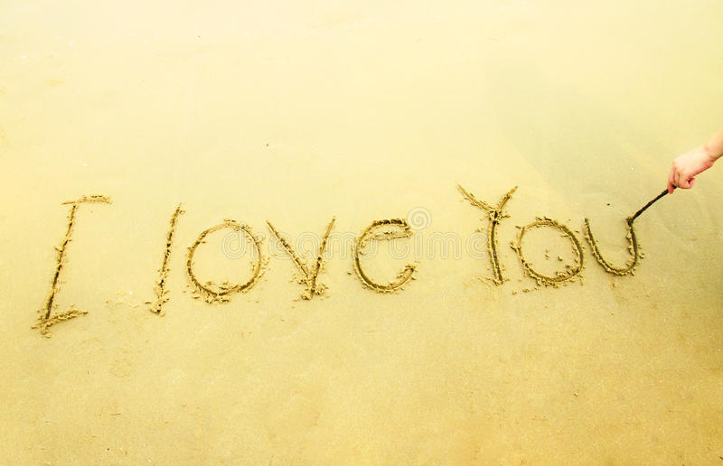 Hand writing I love you on sand and beach stock image