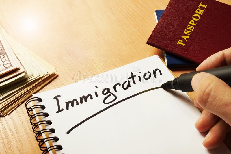 Hand is writing Immigration. Hand is writing Immigration on a note stock images