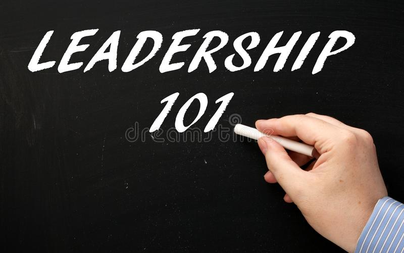 A hand writing Leadership 101 on a blackboard in preparation for learning royalty free stock photo