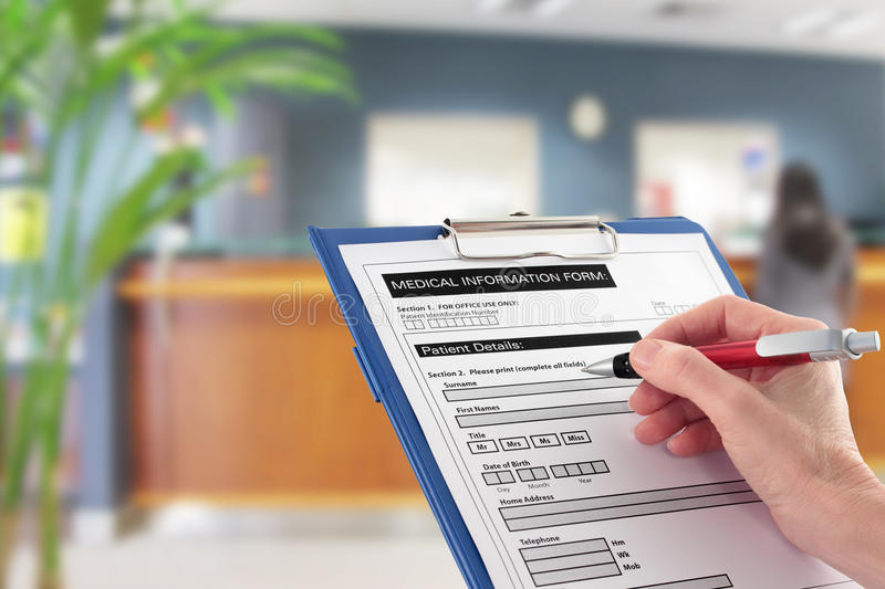 Hand Writing on Medical Details Form in Hospital. A Hand filling in medical information form with blurred hospital reception area in background stock photography