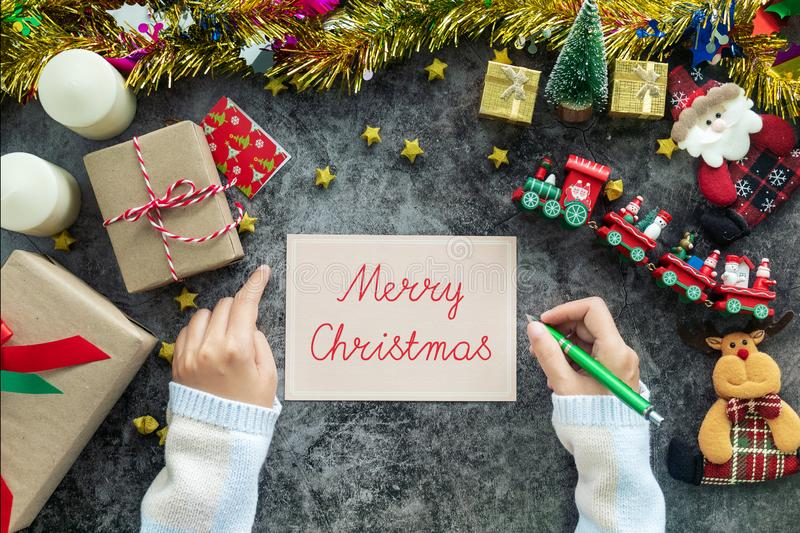 Hand writing Merry Christmas on greeting card during Christmas season and gift festival, decorations with Christmas ornament stock images