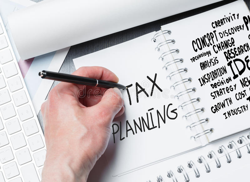 Tax planning concept. Hand writing in notepad placed on desktop with keyboard and other items. Tax planning concept royalty free stock image