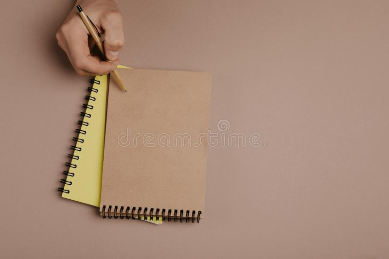 Hand writing in notepad using a pen, on gray background.  stock images