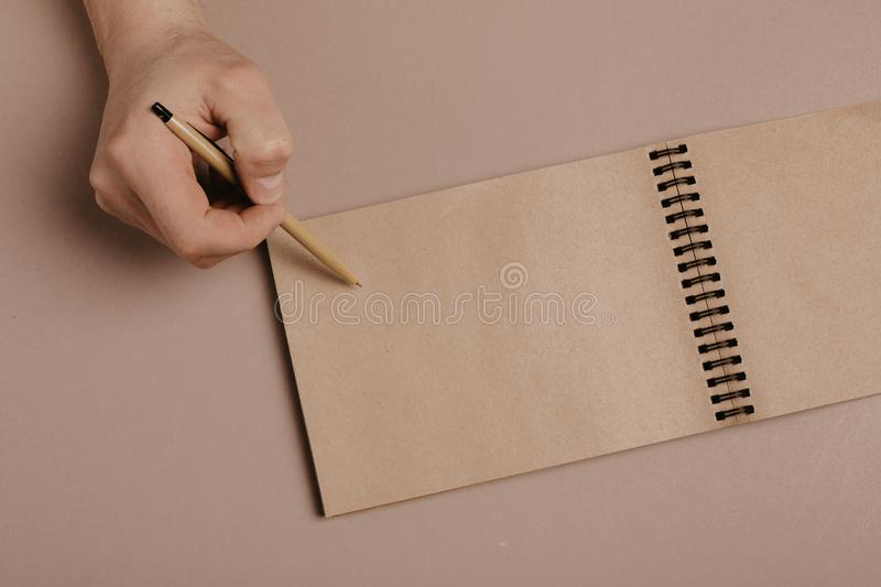Hand writing in notepad using a pen, on gray background.  royalty free stock image
