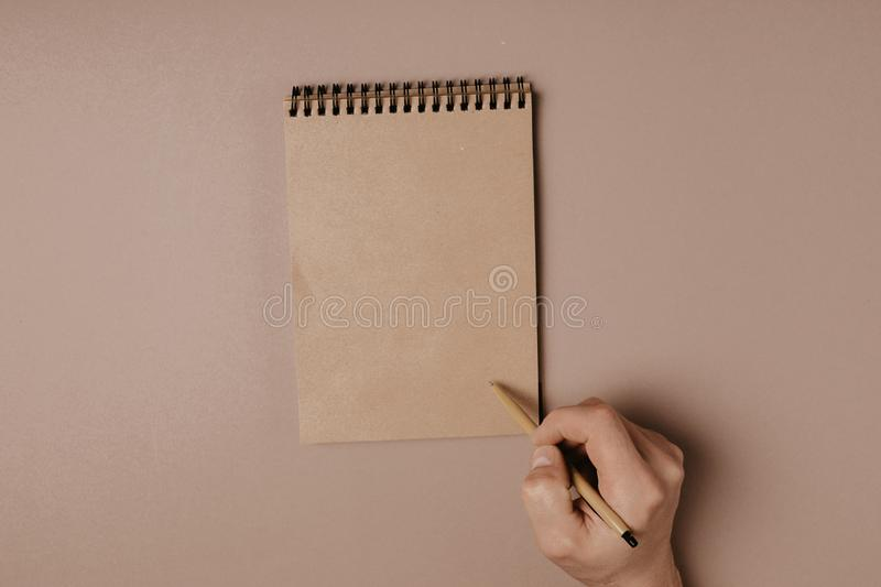 Hand writing in notepad using a pen, on gray background.  royalty free stock photography
