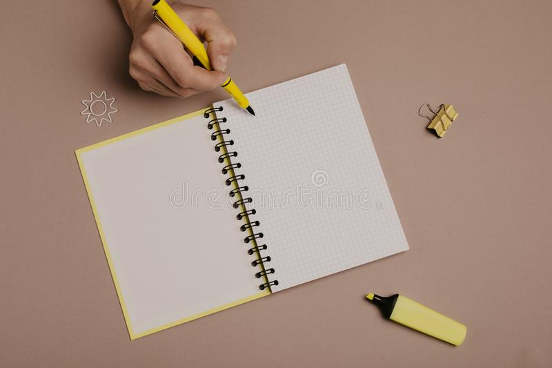 Hand writing in notepad using a pen, on gray background. Hand writing in notepad using yellow pen, on gray background stock image