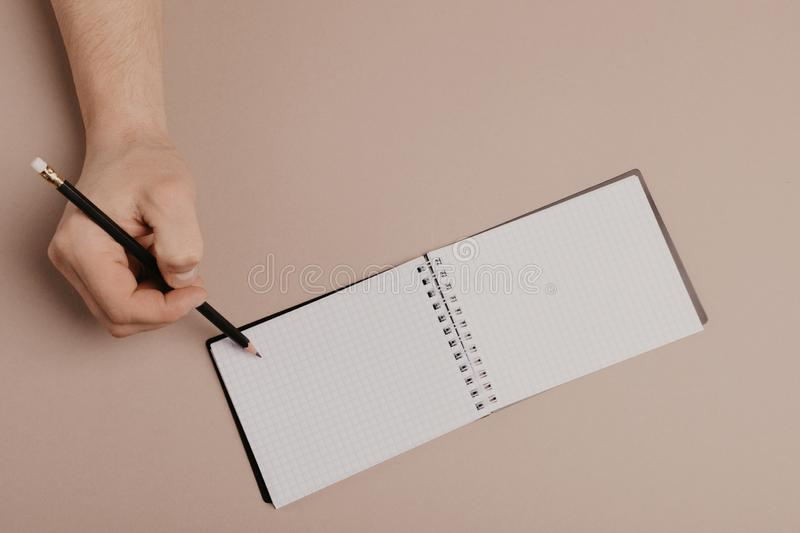 Hand writing in notepad using a pencil, on gray background.  royalty free stock images