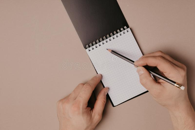 Hand writing in notepad using a pencil, on gray background.  stock photo